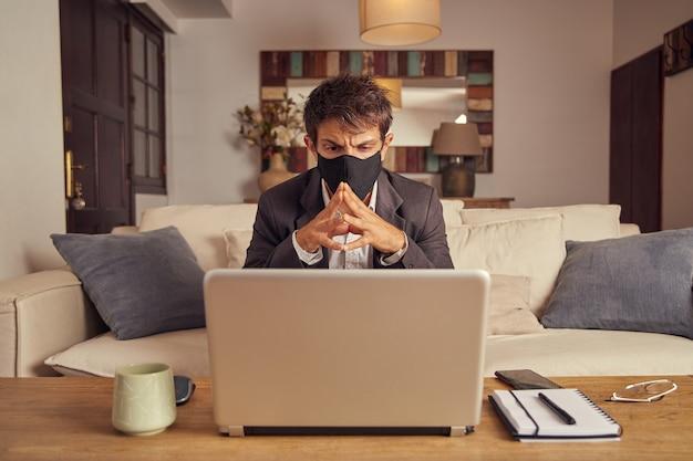 Jonge man werkt in pak werkt videoconferentie vanaf de bank thuis. zwart gezichtsmasker.