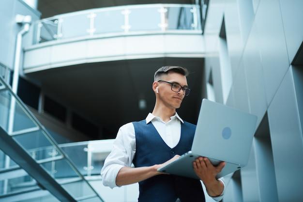 Jonge man werkt op een laptop.