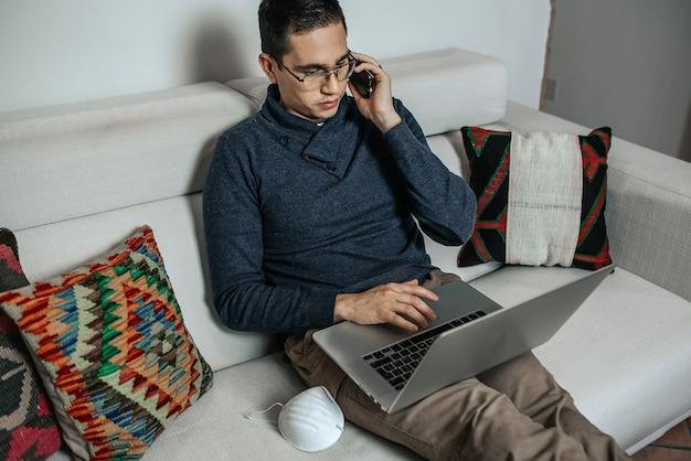 Jonge man werkt thuis zittend op de bank tijdens coronavirus pandemie.