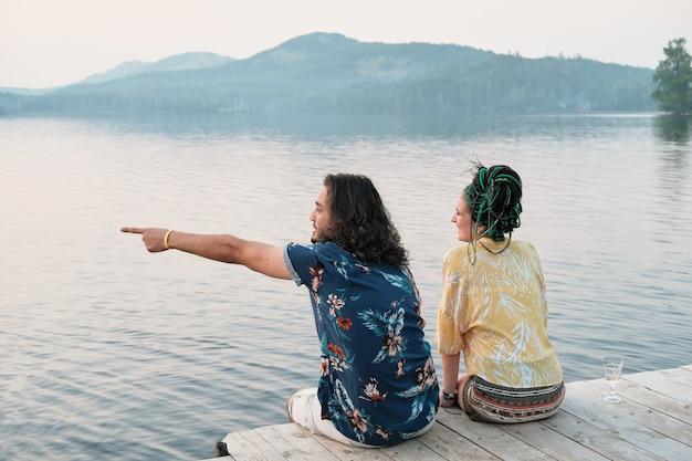 Jonge man wijst en toont iets aan zijn vriendin terwijl ze op een pier zitten en genieten van het uitzicht