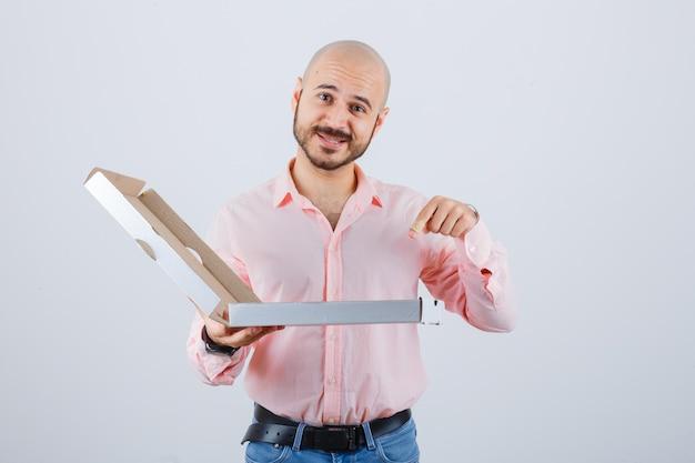 Jonge man wijst geopende pizzadoos in shirt, spijkerbroek en ziet er gelukkig uit. vooraanzicht.
