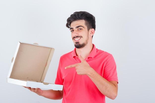 Jonge man wijst geopende pizzadoos in t-shirt en ziet er gelukkig uit, vooraanzicht.