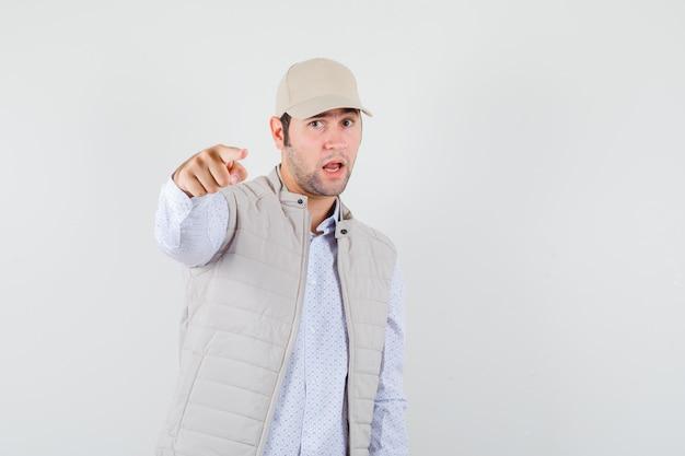 Jonge man wijst in shirt, mouwloos jasje, pet en kijkt serieus. vooraanzicht.