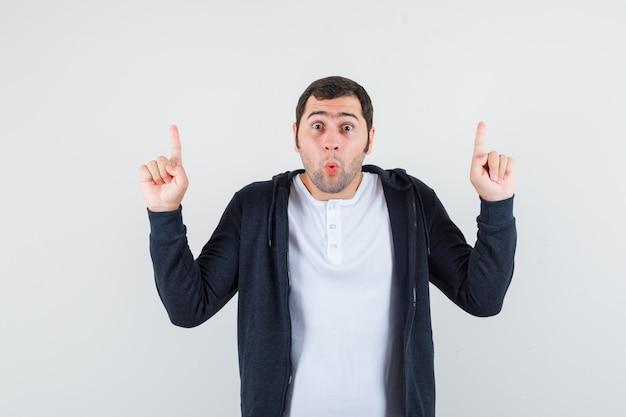 Jonge man wijst met wijsvingers in wit t-shirt en zwarte hoodie met rits aan de voorkant en kijkt verbaasd. vooraanzicht.