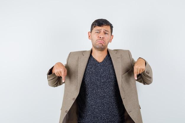 Jonge man wijst naar beneden in grijsachtig bruin jasje, zwart shirt en kijkt boos. vooraanzicht.