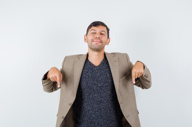Jonge man wijst naar beneden in grijsachtig bruin jasje, zwart shirt en ziet er zelfverzekerd uit, vooraanzicht.