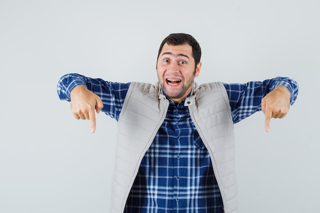 Jonge man wijst naar beneden in shirt, mouwloos jasje en kijkt blij, vooraanzicht.