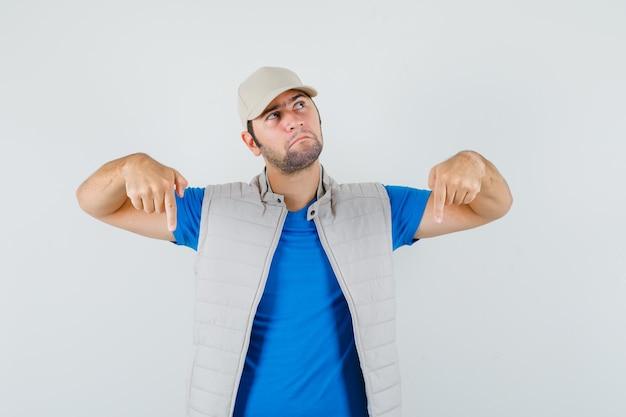 Jonge man wijst naar beneden in t-shirt, jas, pet en kijkt peinzend, vooraanzicht.