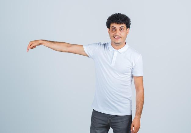Jonge man wijst naar beneden in wit t-shirt, broek en ziet er zelfverzekerd uit, vooraanzicht.