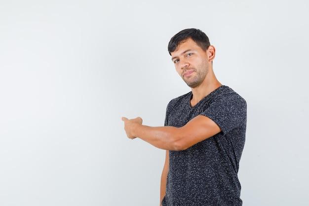 Jonge man wijst naar de achterkant in een zwart t-shirt en ziet er zelfverzekerd uit. vooraanzicht. ruimte voor tekst