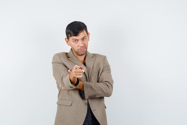 Jonge man wijst naar de camera in grijsachtig bruin jasje, zwart shirt en kijkt geconcentreerd, vooraanzicht. vrije ruimte voor uw tekst