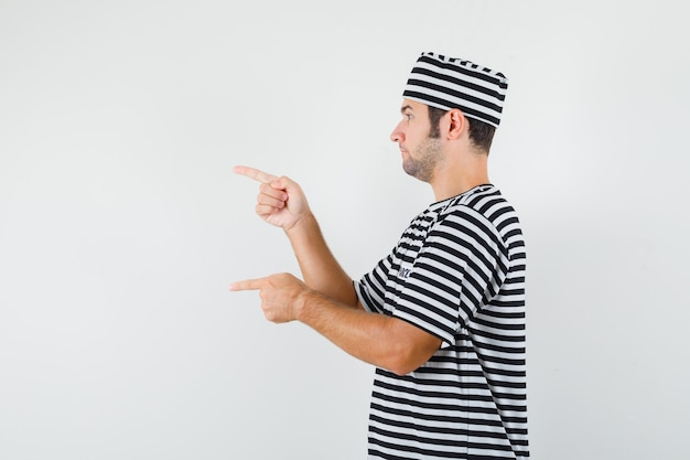 Jonge man wijst naar de linkerkant in t-shirt, hoed en kijkt gefocust.