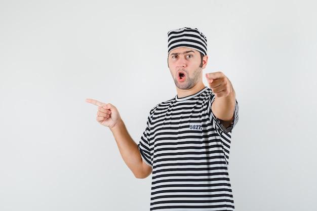 Jonge man wijst naar de linkerkant in t-shirt, hoed en kijkt zelfverzekerd. vooraanzicht.