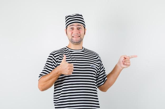 Jonge man wijst naar de rechterkant, duim opdagen in t-shirt, hoed vooraanzicht.