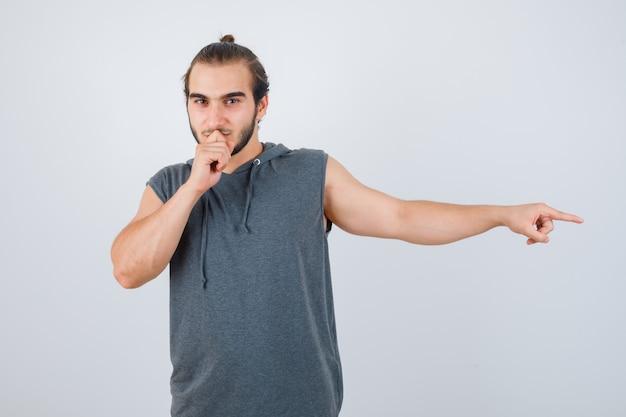 Jonge man wijst naar de zijkant, houdt hand op mond in t-shirt met een kap en ziet er knap uit, vooraanzicht.