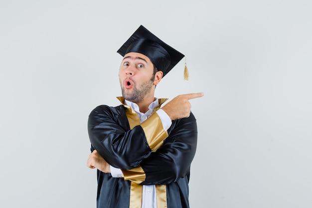Jonge man wijst naar de zijkant in afgestudeerde uniform en kijkt verbaasd. vooraanzicht.