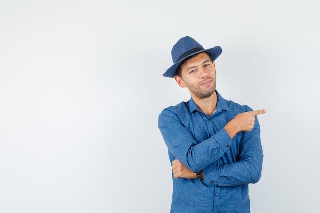 Jonge man wijst naar de zijkant in blauw shirt, hoed en ziet er zelfverzekerd uit, vooraanzicht.
