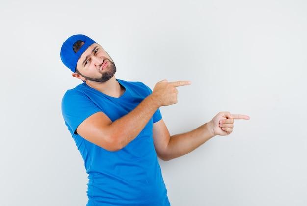 Jonge man wijst naar de zijkant in blauw t-shirt en pet en kijkt ontevreden