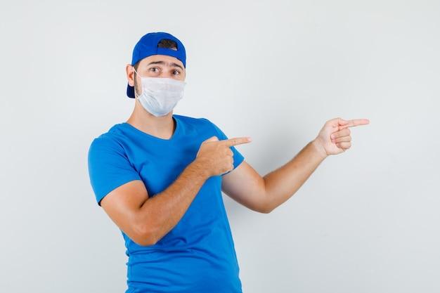 Jonge man wijst naar de zijkant in blauw t-shirt en pet, masker
