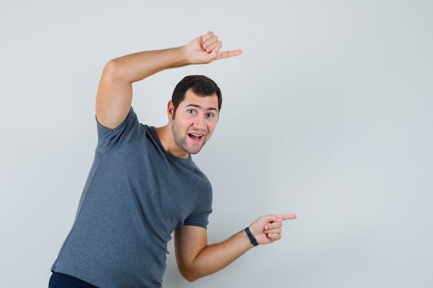 Jonge man wijst naar de zijkant in grijs t-shirt en kijkt dartel