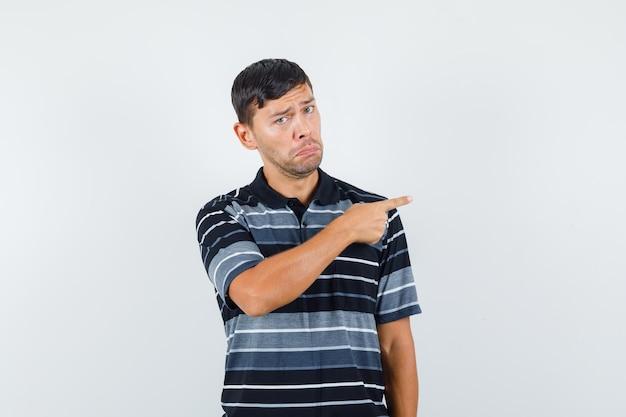 Jonge man wijst naar de zijkant in t-shirt en kijkt teleurgesteld, vooraanzicht.
