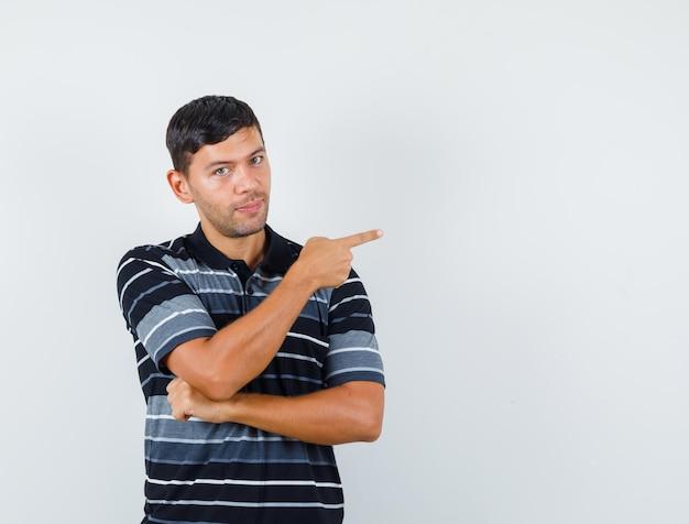 Jonge man wijst naar de zijkant in t-shirt en ziet er zeker uit. vooraanzicht.