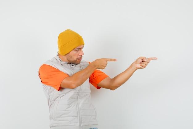 Jonge man wijst naar de zijkant in t-shirt, jasje, hoed en kijkt gefocust