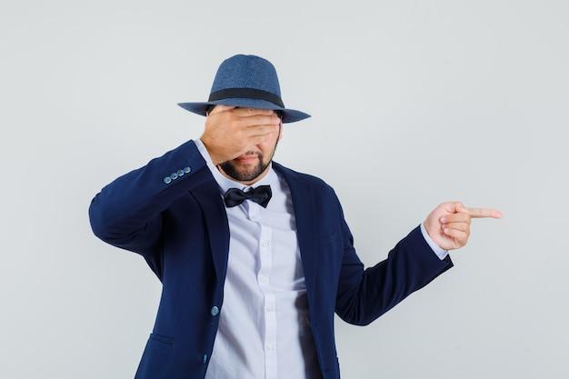 Jonge man wijst naar de zijkant met bedekte ogen in pak, hoed vooraanzicht.
