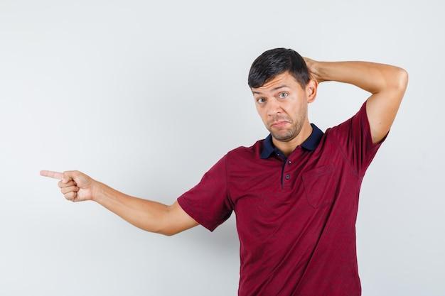 Jonge man wijst naar de zijkant met de hand achter het hoofd in een t-shirt en kijkt aarzelend. vooraanzicht.