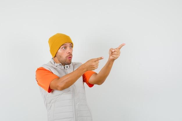 Jonge man wijst naar de zijkant met vingers omhoog in t-shirt, jas, hoed en kijkt verbaasd.