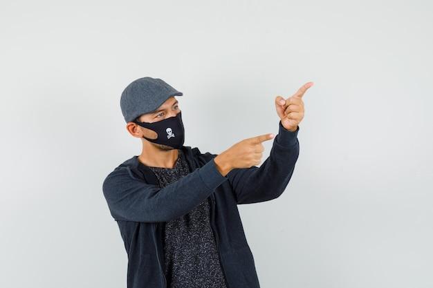 Jonge man wijst naar de zijkant met vingers omhoog in t-shirt, jas, pet, masker en kijkt gefocust.