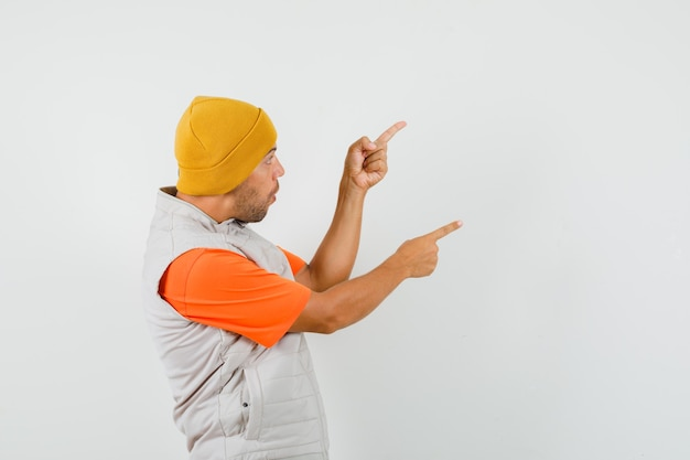 Jonge man wijst naar de zijkant met vingers omhoog in t-shirt, jasje, hoed en kijkt verbaasd.
