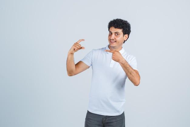 Jonge man wijst naar iets kleins in wit t-shirt, broek en ziet er vrolijk uit. vooraanzicht.