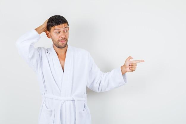 Jonge man wijst naar kant met hand achter hoofd in witte badjas vooraanzicht.