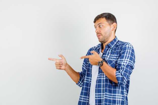 Jonge man wijst naar kant met pistoolgebaar in overhemd en kijkt bang, vooraanzicht.
