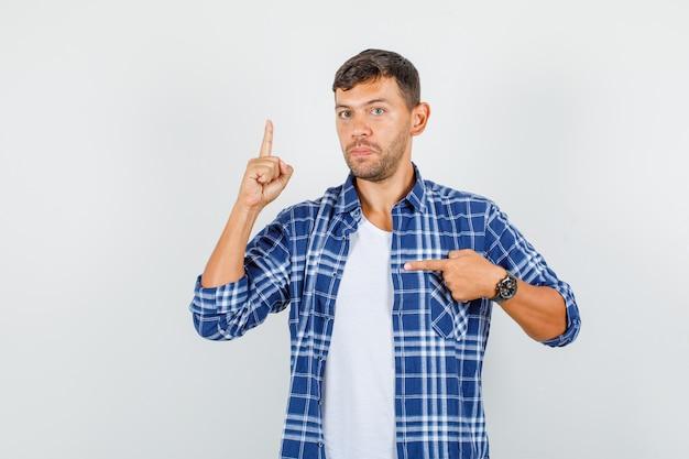 Jonge man wijst naar kant met vinger omhoog in shirt en kijkt streng, vooraanzicht.
