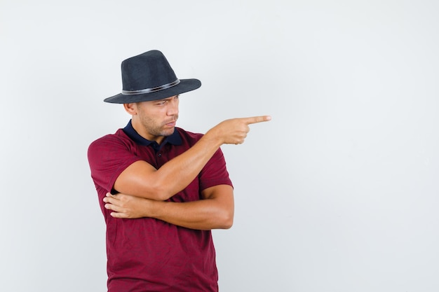 Jonge man wijst naar links in rood shirt, zwarte hoed en kijkt serieus, vooraanzicht. ruimte voor tekst