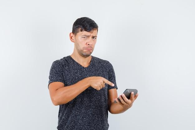 Jonge man wijst naar rekenmachine in zwart t-shirt en kijkt boos, vooraanzicht.