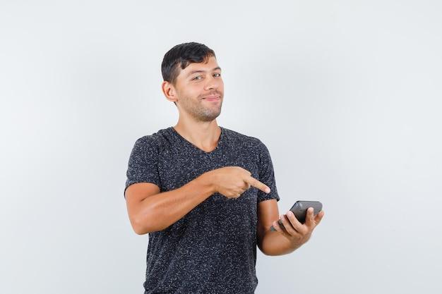 Jonge man wijst naar rekenmachine in zwart t-shirt en ziet er ontspannen uit. vooraanzicht.
