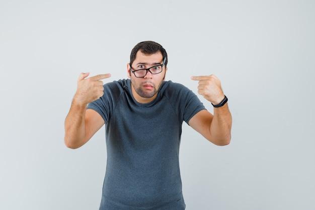 Jonge man wijst naar zichzelf in grijs t-shirt en kijkt verward