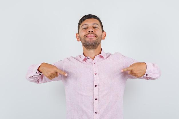 Jonge man wijst naar zichzelf in roze shirt en kijkt zelfverzekerd. vooraanzicht.