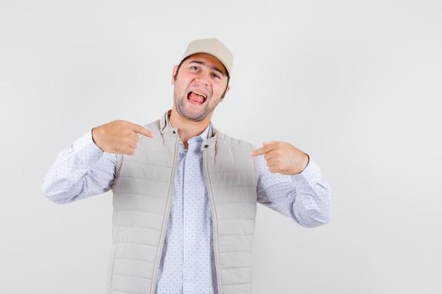 Jonge man wijst naar zichzelf in shirt, mouwloos jasje, pet en kijkt zelfverzekerd. vooraanzicht.