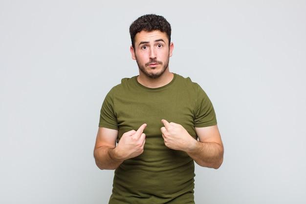 Jonge man wijst naar zichzelf met een verwarde en vragende blik, geschokt en verrast om gekozen te worden