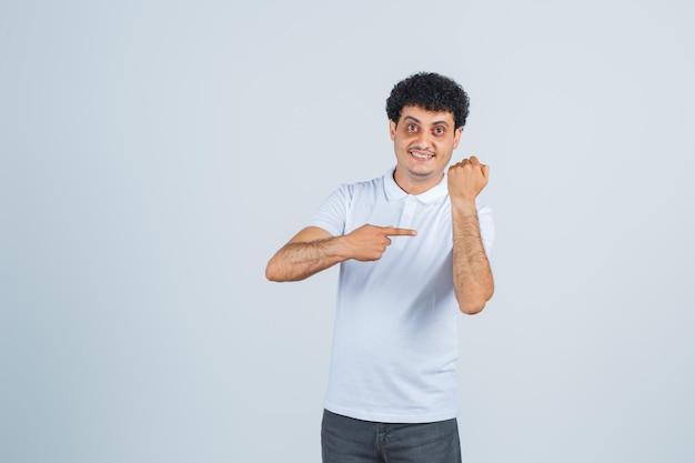 Jonge man wijst naar zijn arm in wit t-shirt, broek en ziet er vrolijk uit, vooraanzicht.