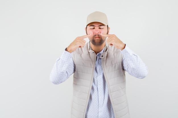 Jonge man wijst naar zijn neus in shirt, mouwloos jasje, pet en kijkt gefocust. vooraanzicht.