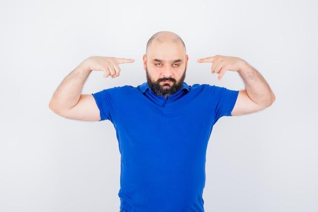 Jonge man wijst naar zijn oren in blauw shirt en kijkt nerveus, vooraanzicht.