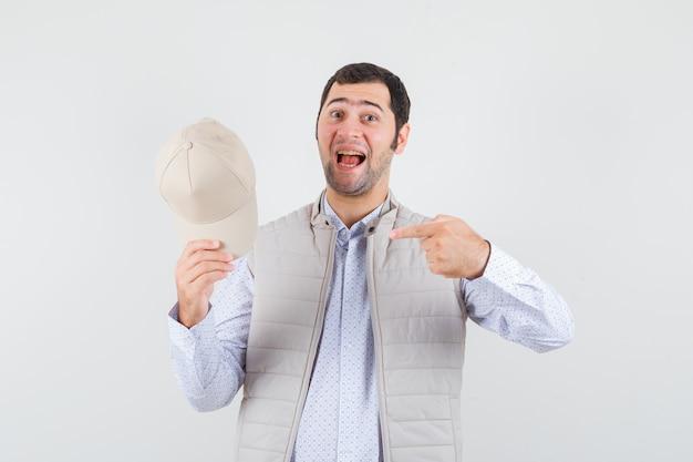 Jonge man wijst naar zijn pet in shirt, mouwloos jasje en kijkt optimistisch. vooraanzicht.