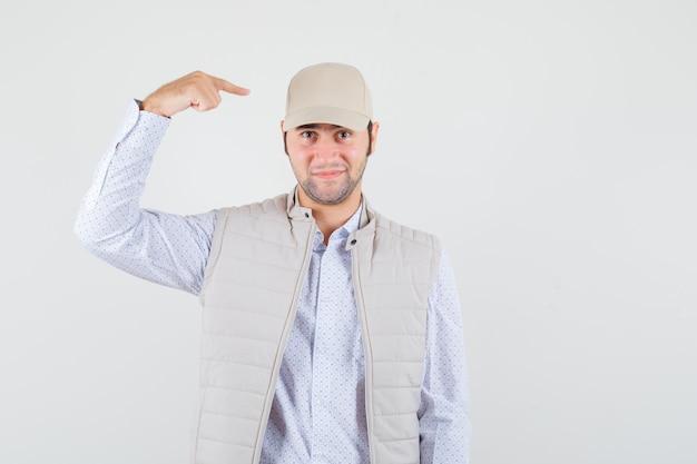 Jonge man wijst naar zijn pet in shirt, mouwloos jasje, pet en kijkt blij. vooraanzicht.