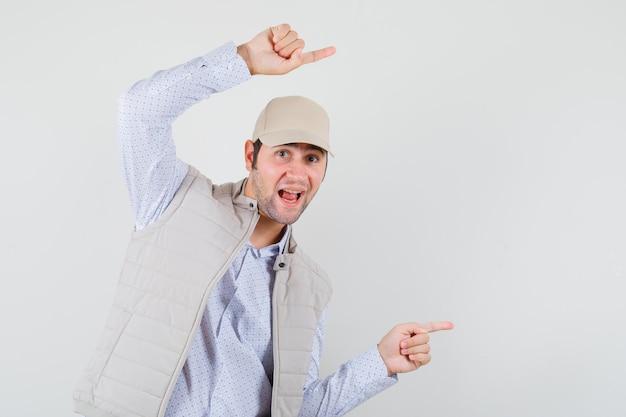 Jonge man wijst opzij boven zijn hoofd in shirt, mouwloos jasje, pet en kijkt gefocust, vooraanzicht.