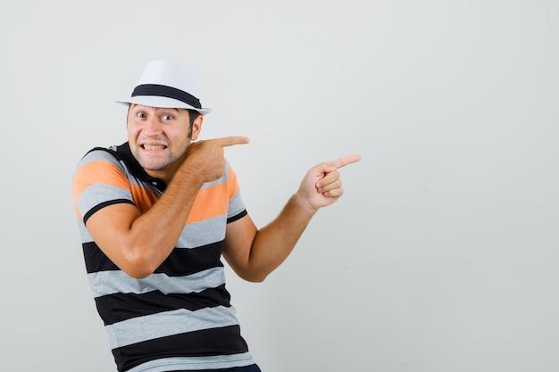 Jonge man wijst opzij in gestreept t-shirt, hoed en zoekt gekke ruimte voor tekst